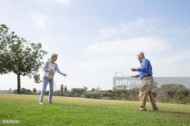 Senior couple playing badminton in park