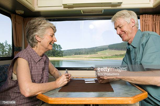 Senior couple playing cards in caravan