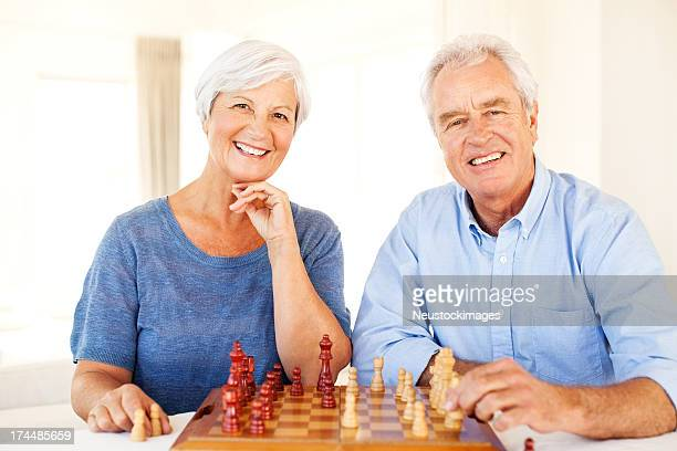 Senior Couple Playing Chess Together At Dining Table