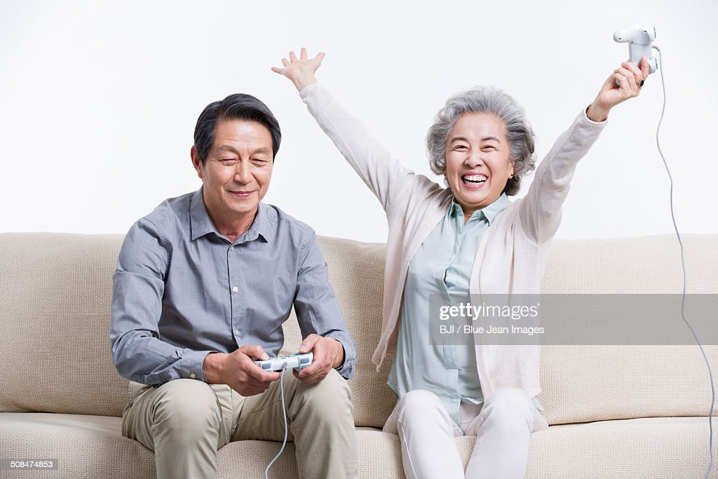 Senior couple playing video game in living room