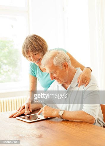 Senior couple playing with a digital tablet : Stock Photo