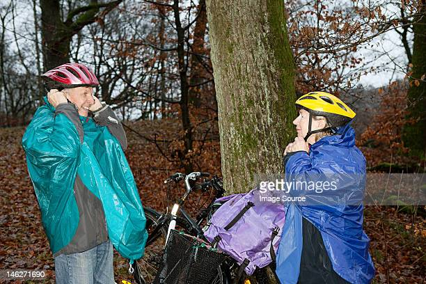 Senior couple preparing to cycle in forest
