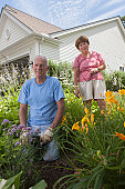 Senior couple preparing to plant flowers in garden