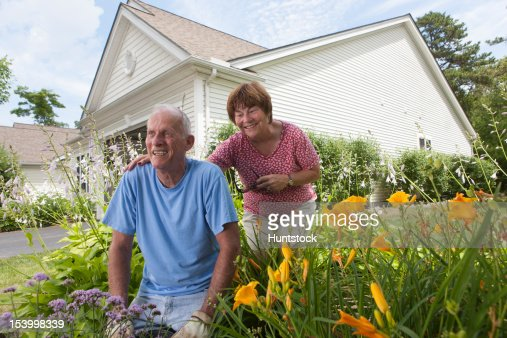 Senior couple preparing to plant flowers in garden : Stock Photo