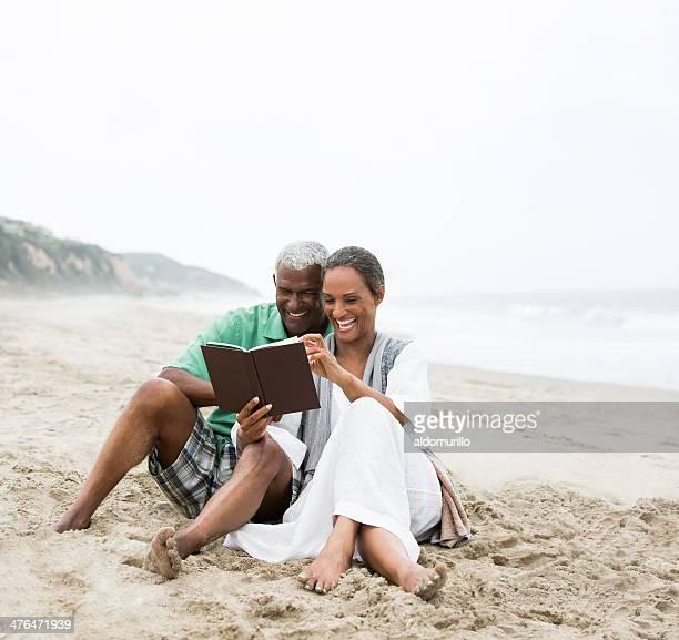 Coppia Senior leggendo sulla spiaggia