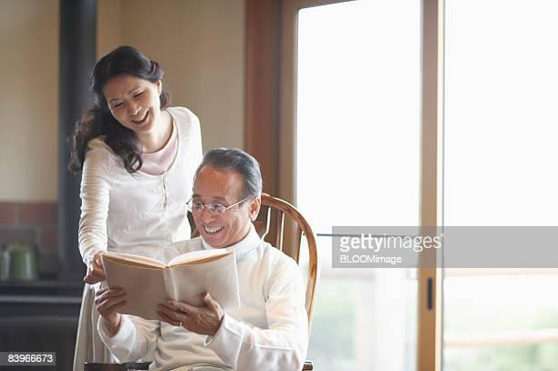 Senior couple reading book, smiling