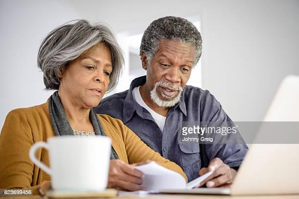Senior couple reading document with laptop