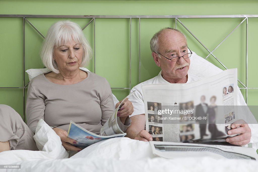 Senior couple reading in bed : Stock Photo