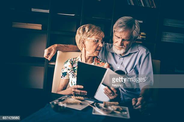 Senior Couple Reading Journal in Confectionary in Summer Morning
