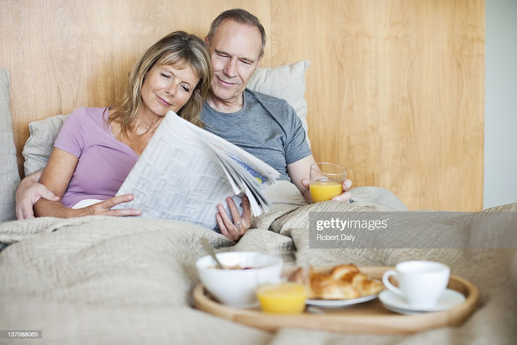 Senior couple reading newspaper and having breakfast in bed : Stock Photo