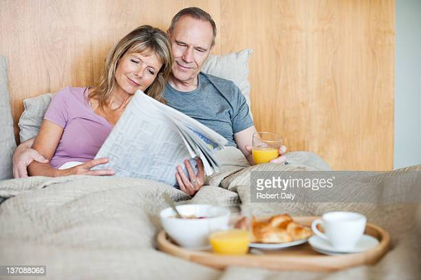 Senior couple reading newspaper and having breakfast in bed