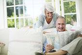 Senior couple reading newspaper on sofa