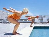 Senior couple ready to dive in to swimming pool