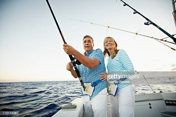 Senior couple reeling in fish on fishing boat