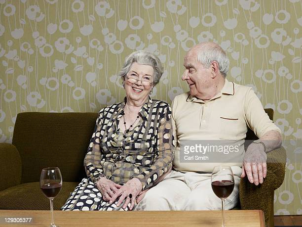 Senior couple relaxed on couch with two glasses of wine on the table