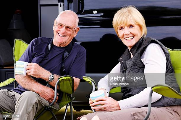 Senior couple relaxing around camper van