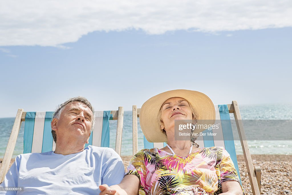 senior couple relaxing in deckchairs on beach. : Stock-Foto