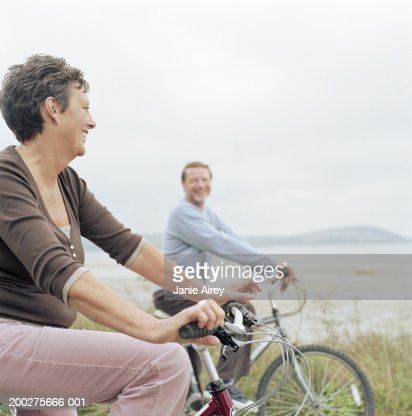 Senior couple riding bicycles by sea, smiling : Stock Photo