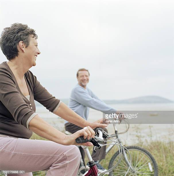 Senior couple riding bicycles by sea, smiling