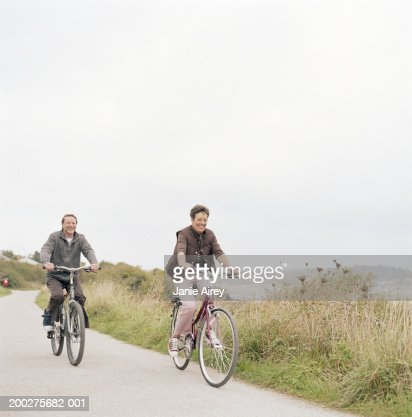 Senior couple riding bicycles on path by sea, smiling : Stock Photo