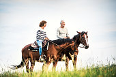 A happy senior couple riding horses on a meadow in nature.