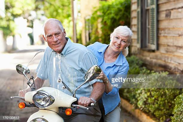 Senior couple riding motor scooter