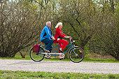 Senior couple riding tandem bike in park
