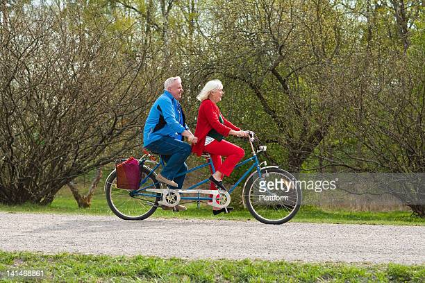 Senior couple riding tandem bike in park