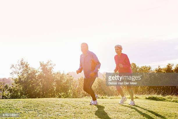 Senior couple running, exercising outdoors.