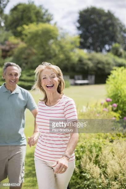 Senior couple running in backyard