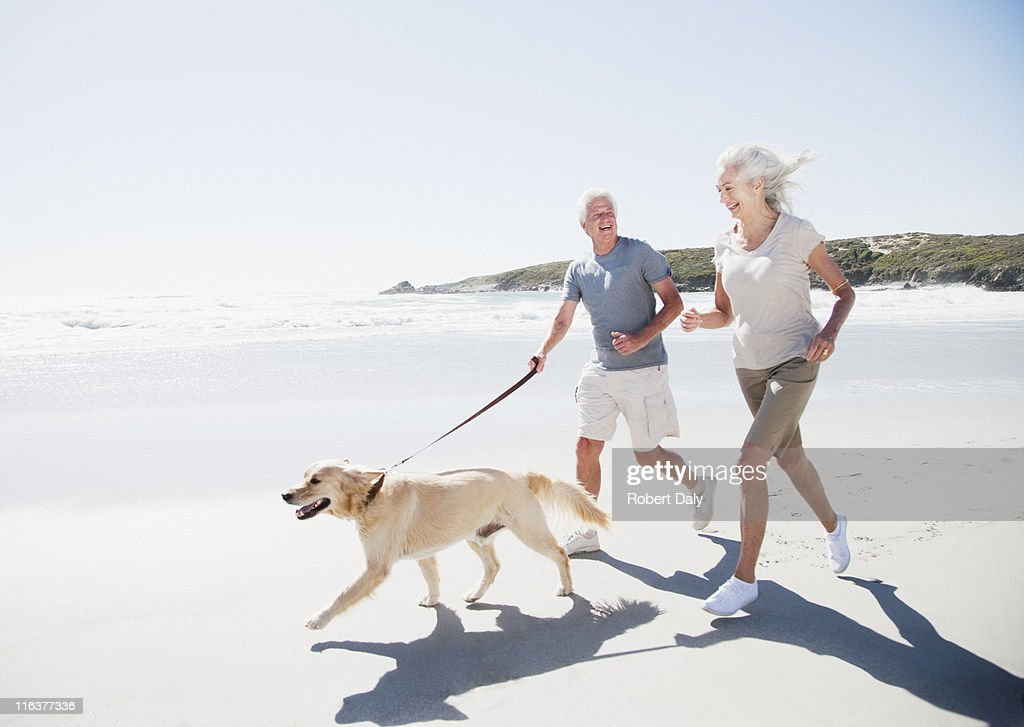 Senior couple running on beach with dog : Stock Photo
