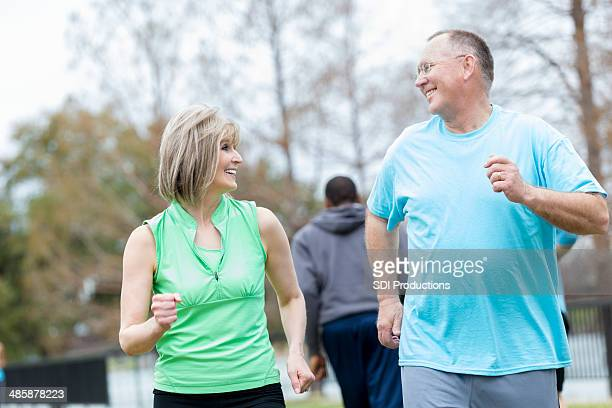 Senior couple running together in a park