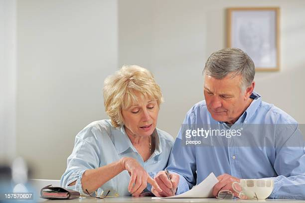 Senior couple sat at a table doing paperwork