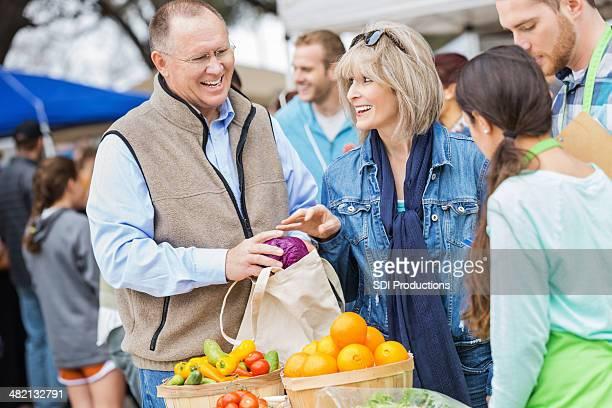 Coppia Senior selezione di prodotti al mercato degli agricoltori locali booth