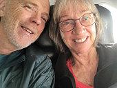 Senior couple selfie in airplane seats beside window
