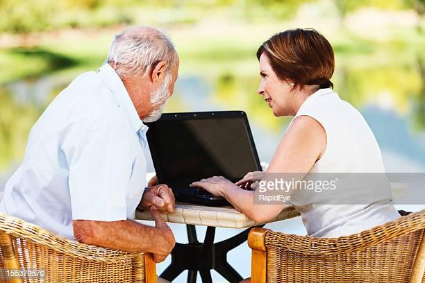 Senior couple share a laptop computer in garden setting