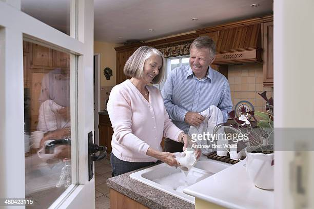 Senior couple share washing up at home