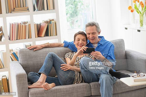 Senior couple sharing cell phone on sofa