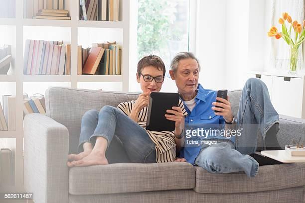 Senior couple sharing electronic devices on sofa