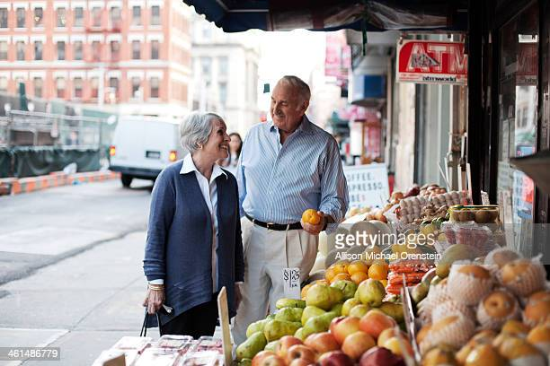 senior couple shopping for food at fruit stand