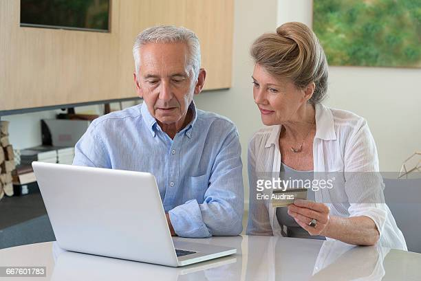 Senior couple shopping online with laptop at home