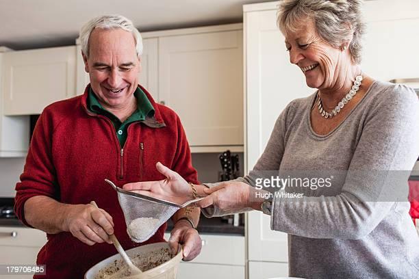 Senior couple sieving flour into mixing bowl
