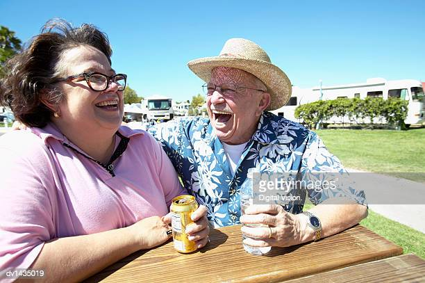 Senior Couple Sit at a Table at a Campsite Holding Drinks and Laughing