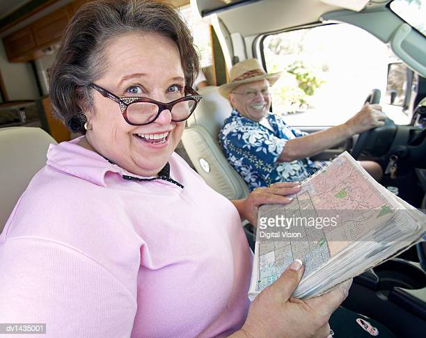 Senior Couple Sit in the Front Seat of a Motor Home, Woman Holding a Map and Smiling