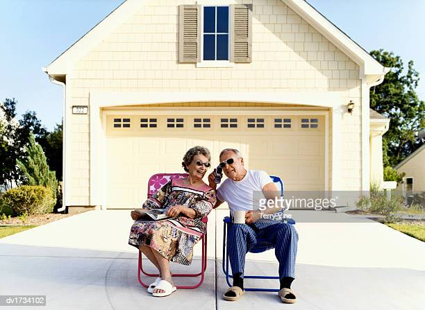 Senior Couple Sit on Chairs Outside Their House Listening to a Mobile Phone