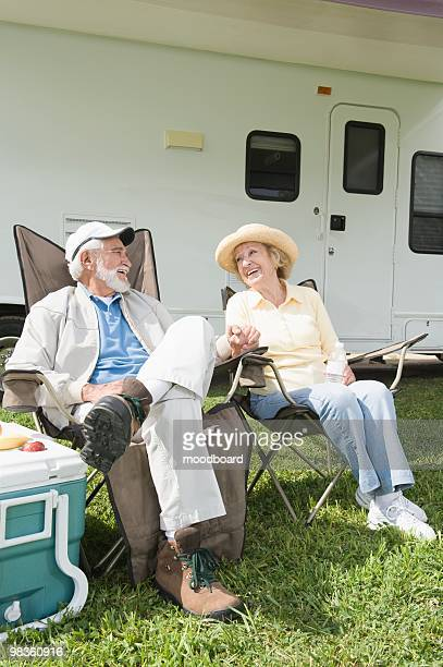 Senior couple sit outside RV home