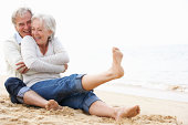 Senior Couple Sitting On Beach Together Laughing