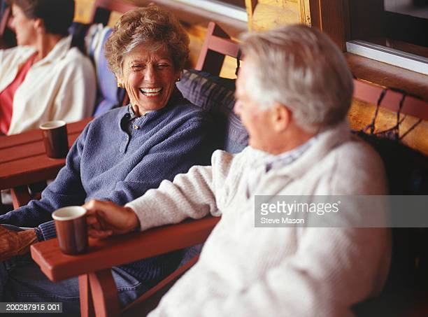 Senior couple sitting at cafe at mountain lodge