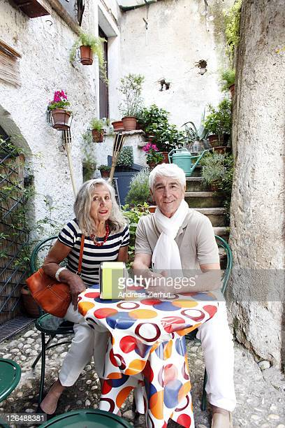 Senior couple sitting at table outdoors, Italy