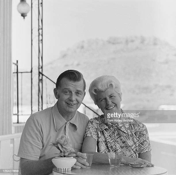 Senior couple sitting at table, smiling, portrait